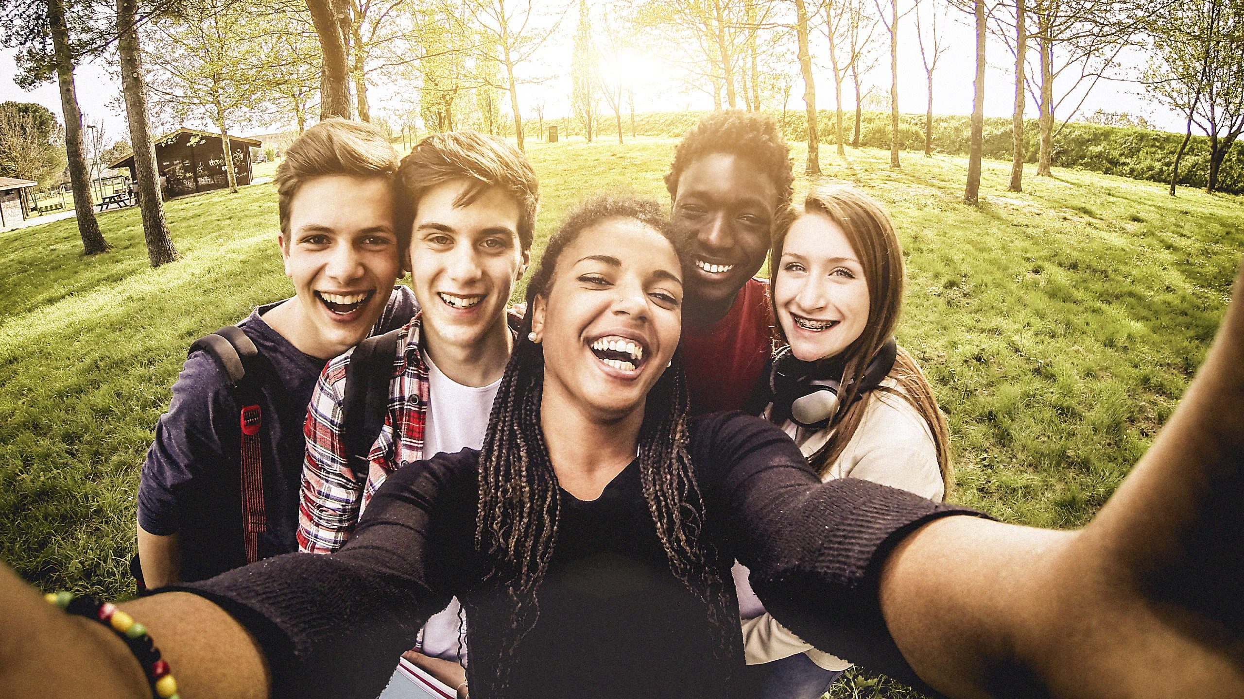 Image is a photo of 5 adolescents, smiling outdoors, holding a globe