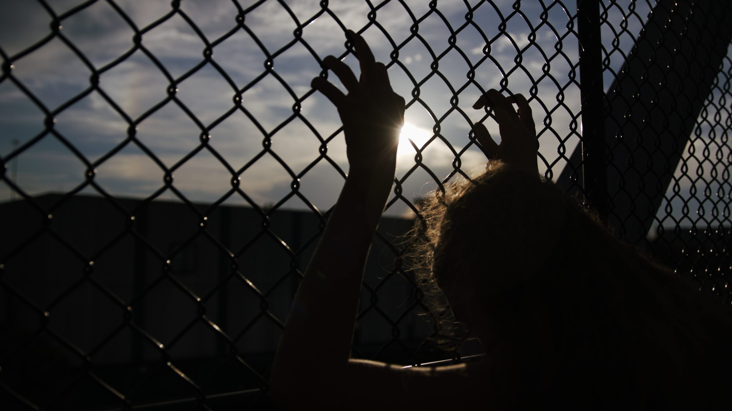 Image of a person holding on chain link fence.